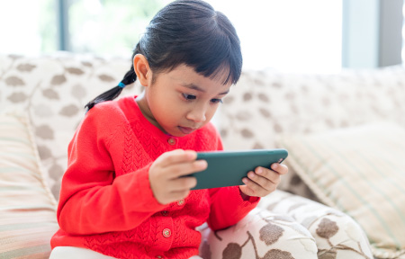 Little girl sitting on couch watching smartphone