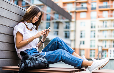 Teen girl sitting outside using social media on smartphone