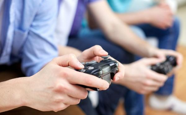 Hands of multiple people using controllers to play video games