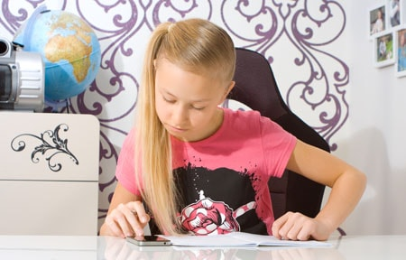 Girl sitting at desk using smartphone to help with homework