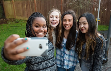 Four teen girls standing outside smiling and taking a selfie together