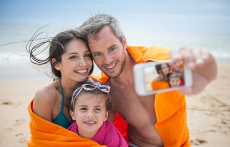 Mom dad and daugther wrapped in towels taking family selfie at the beach with a smartphone