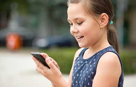 Smiling little girl standing outside using smartphone