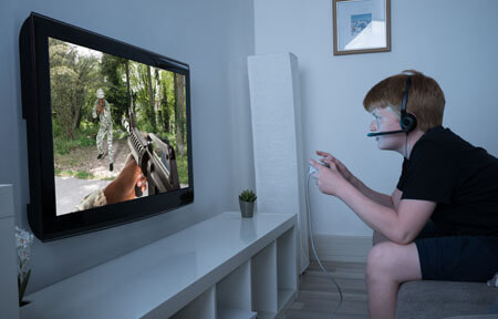 Boy sitting in living room at home close to the tv playing an online video game and wearing a headset