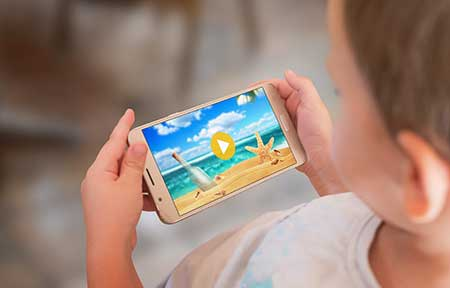 Over the shoulder view of child watching beach video on smartphone