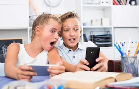 Boy and girl sitting at table looking shocked at video sharing apps used on smartphones