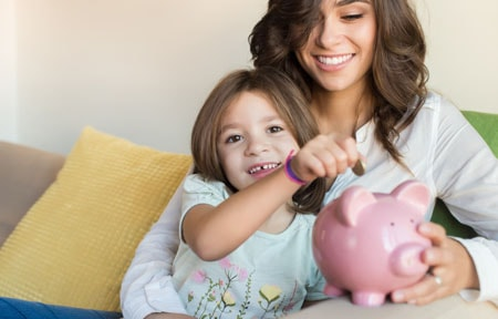 Mom and daughter sitting together while daughter adds a coin to piggy bank