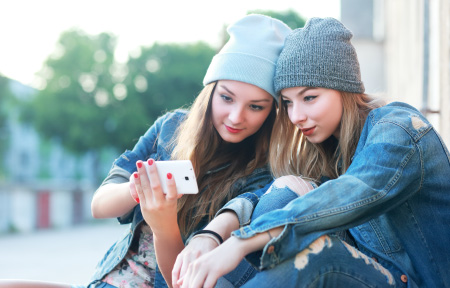 Two teen girls sitting outside taking selfies on smartphone