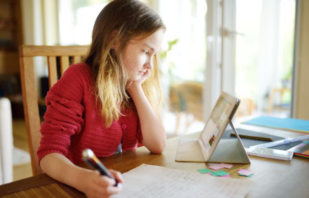 Young girl sitting at table looking at blocked website on tablet while doing homework