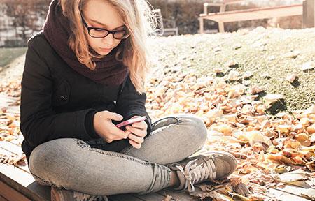 Teen girl sitting outside using social media on smartphone
