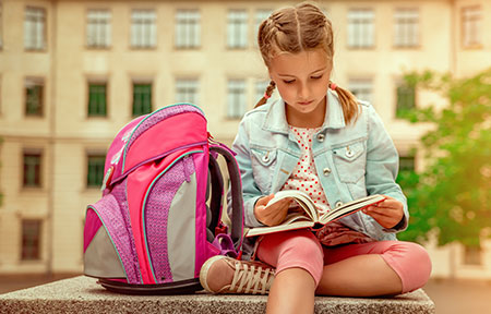 Young girl sitting outside of school with backpack reading a book