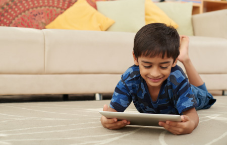 Boy laying on ground streaming video on tablet