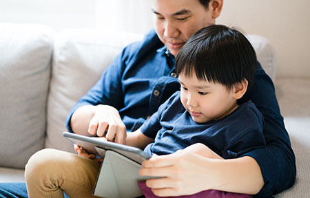 Father and young boy sitting on couch using tablet