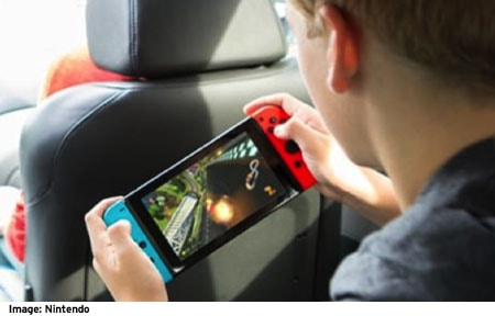 Over the shoulder view of a boy playing a video game on the nintendo switch during a car ride
