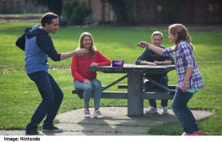 Family playing nintendo switch outside at a picnic table