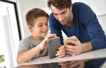 Father and son looking at smartphones together at table