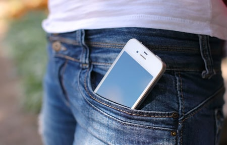 Close up of teen girls smartphone in front pocket of jeans while standing outside