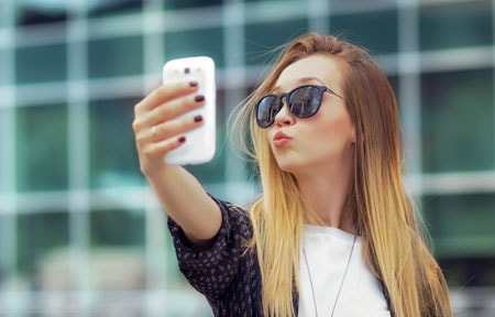 Teen girl standing outside taking a selfie on a smartphone