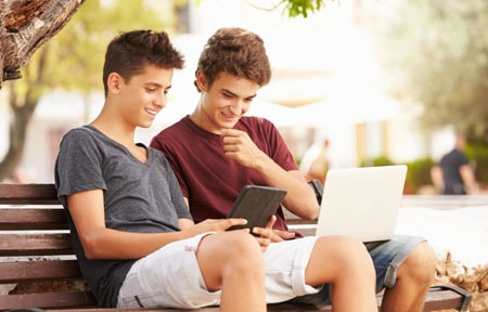 Two teen boys sitting on bench under tree looking at a laptop and tablet