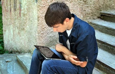 Teen boy sitting on steps outside looking concerned while using a tablet