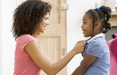 Mom helping daughter button dress during morning routine before school