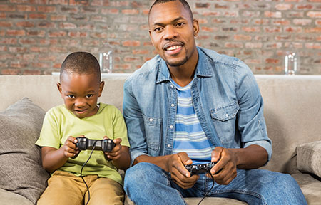 Dad and young son sitting on couch holding controllers and playing a video game