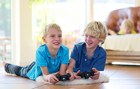 Two young boys laying on carpet with controllers playing video games on PS4