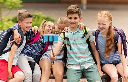Five girls and boys sitting outside on a bench taking selfie using a selfie stick