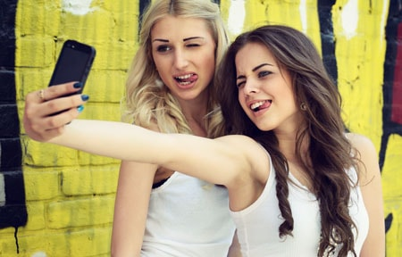 Two teen girls standing in from of yellow background making faces and taking a selfie