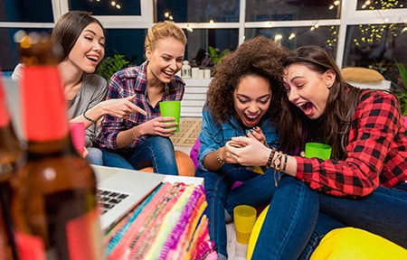 Four teen girls laughing at photos on a smartphone during a party