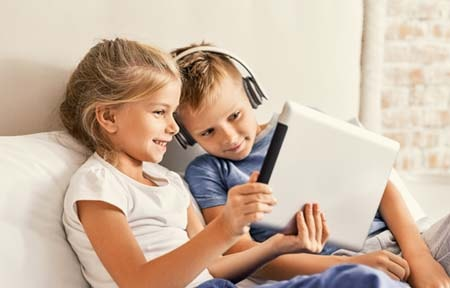 Boy wearing headphones and girl sitting on couch watching youtube on tablet