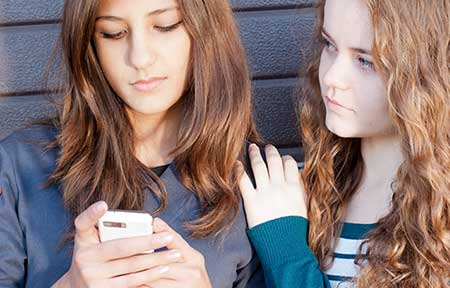 Teen girl looking at smartphone and friend comforting her
