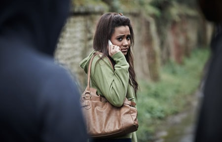 Teen girl looking scared using a smartphone to make a call while two dark figures pursue her
