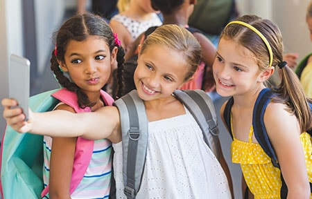 Three young girls wearing backpacks and taking a seflie in a busy school hallway with other kids in the background