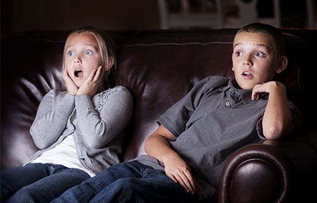 Young boy and girl sitting on couch watching TV and looking shocked by profanity