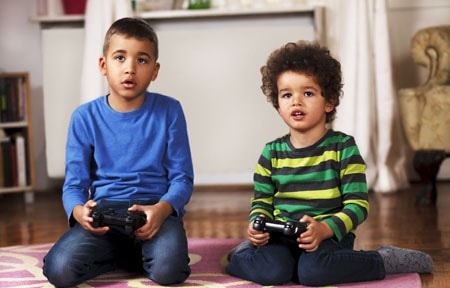 Two young boys sitting on the floor holding controllers and playing a video game