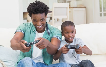 Father and son sitting on couch using controllers to play a video game