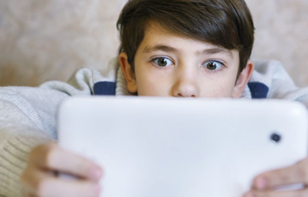 Young boy using tablet and looking shocked at what he sees